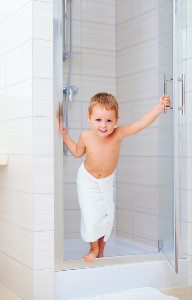 cute kid ready to wash himself in shower