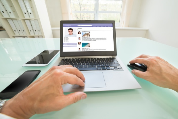 Close-up Of A Person Chatting On Social Website In Office. Photographer owns copyright for images on screen